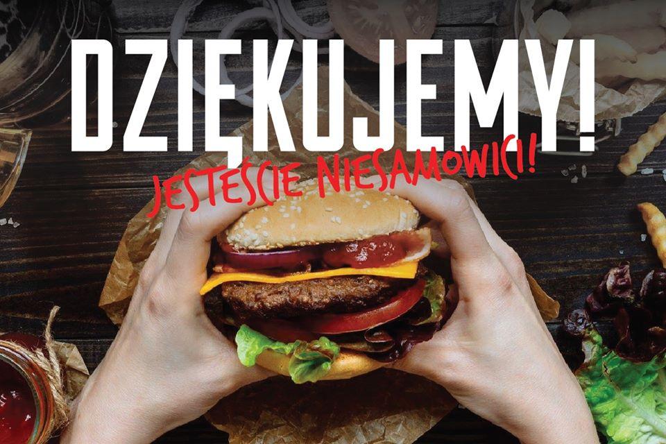"""Grafika z napisem """"Dziękujemy! Jesteście niesamowici!"""" - tłem napisu jest zdjęcie dłoni trzymających burgera jak do ugryzienia."""