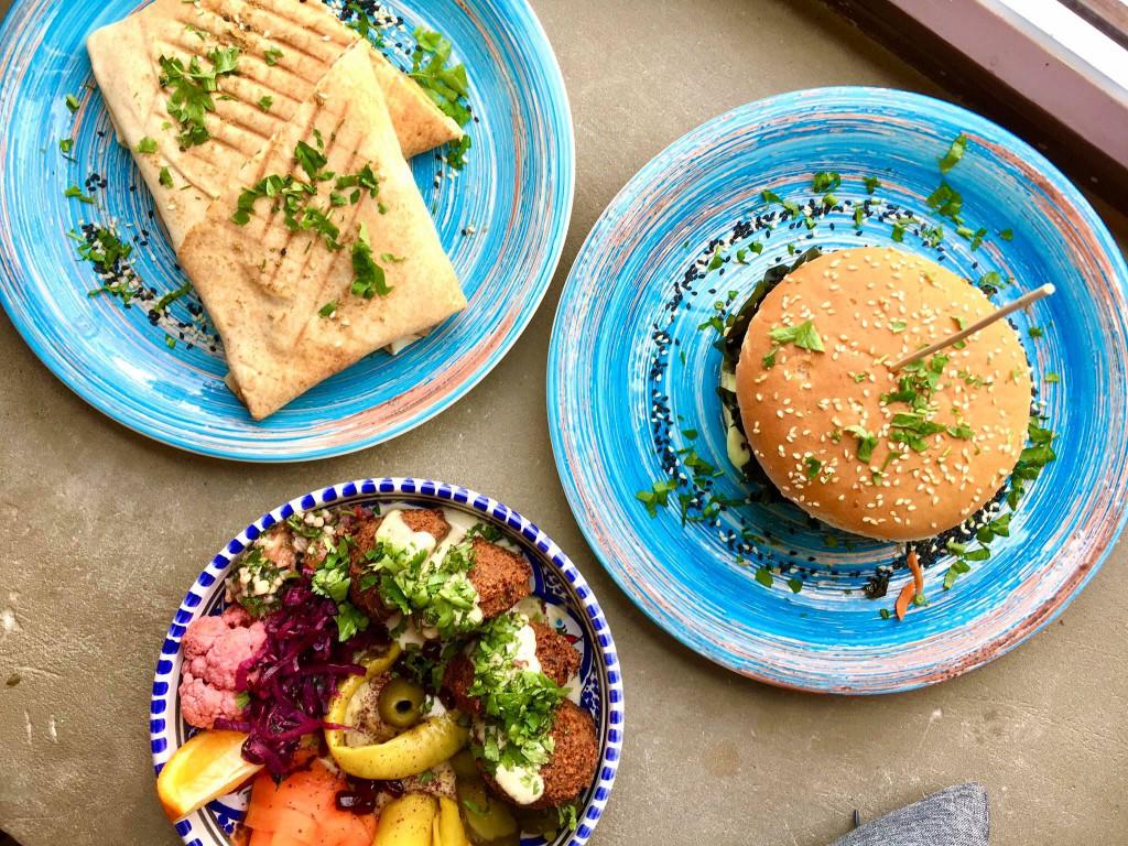 Zdjęcie zrobione z góry - widać na nim trzy talerze z wegańskim jedzeniem w restauracji Falla.