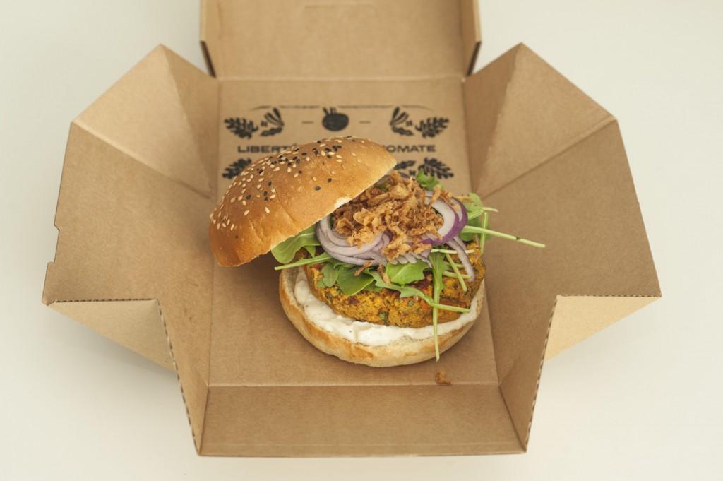 Na zdjęciu widać rozłożone, tekturowe pudełko, na którym leży burger z restauracji Plantacja. Pudełko sprawia wrażenie złożonego jak origami.