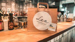 Na zdjęciu widać blat baru w restauracji Len i Bawełna, na którym stoi papierowa torba z jedzeniem na wynos. Zdjęcie wykonał Krzysztof Rosiak.