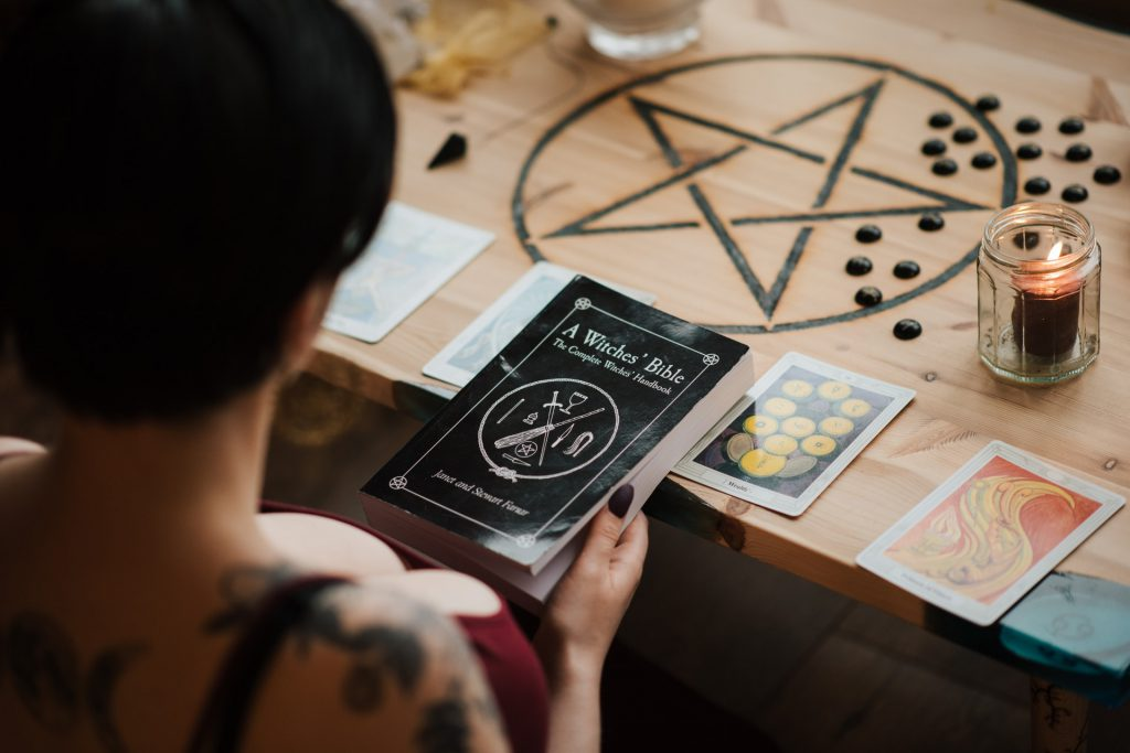 """Na zdjęciu widać stół z rozłożonymi kartami tarota, świecą i narysowanym pentagramem. Przy stole siedzi kobieta - na zdjęciu widać jej ramię i dłoń trzymającą książkę pt. """"Wtches' Bible""""."""