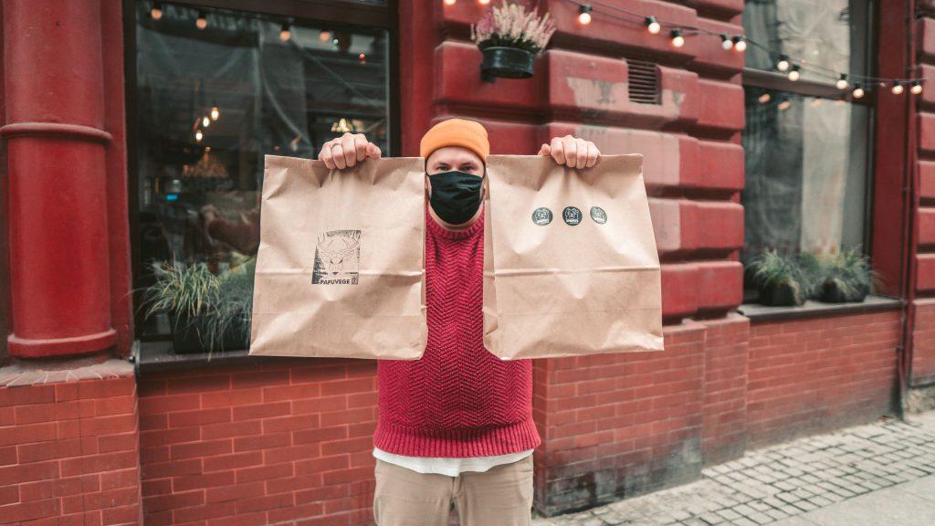Zdjęcie przedstawia Damiana Stankiewicza, szefa kuchni i menedżera restauracji Umamitu by Papuvege. Damian stoi przed lokalem w maseczce na twarzy, w wyciągniętych przed siebie rękach trzyma dwie papierowe torby z jedzeniem w dostawie.