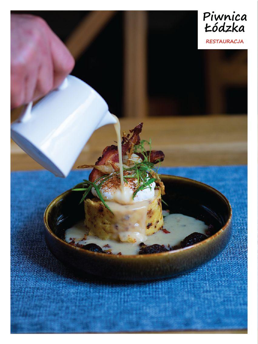 Na zdjęciu znajduje się miska z zalewajką, nad którą widać dłoń wlewającą zupę do miski. W prawym górnym rogu zdjęcia znajduje się logo restauracji Piwnica Łódzka.
