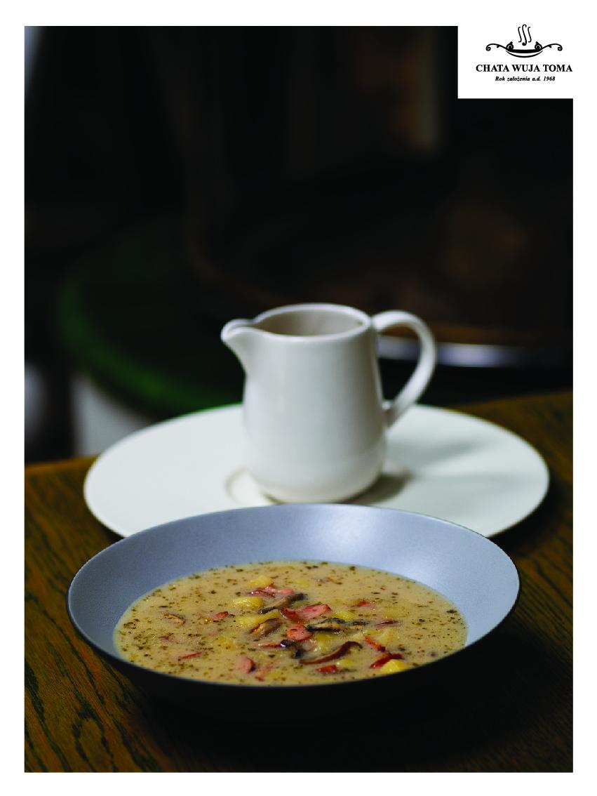 Na zdjęciu widać głęboki talerz z zalewajką. Za nim stoi biały dzbanek. W prawym górnym rogu zdjęcia znajduje się logo restauracji Chata Wuja Toma.
