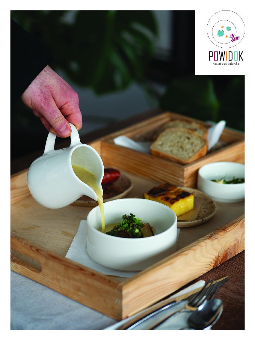 Na zdjęciu widać drewnianą tacę, na której ułożone są miseczki i talerze, w których znajduje się jedzenie. Na pierwszym planie widać dłoń nalewającą z dzbanka zupę do jednej z misek. W prawym górnym rogu widnieje logo restauracji Powidok