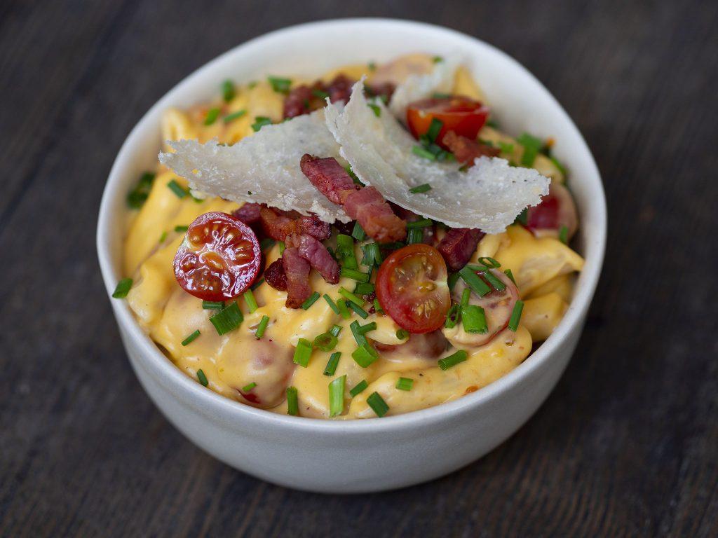 Na zdjęciu widać białą, głęboką, ceramiczną miseczkę, w której znajduje się danie z pszennego makaronu penne w serowym sosie z kawałkami smażonego boczku i pomidorkami.