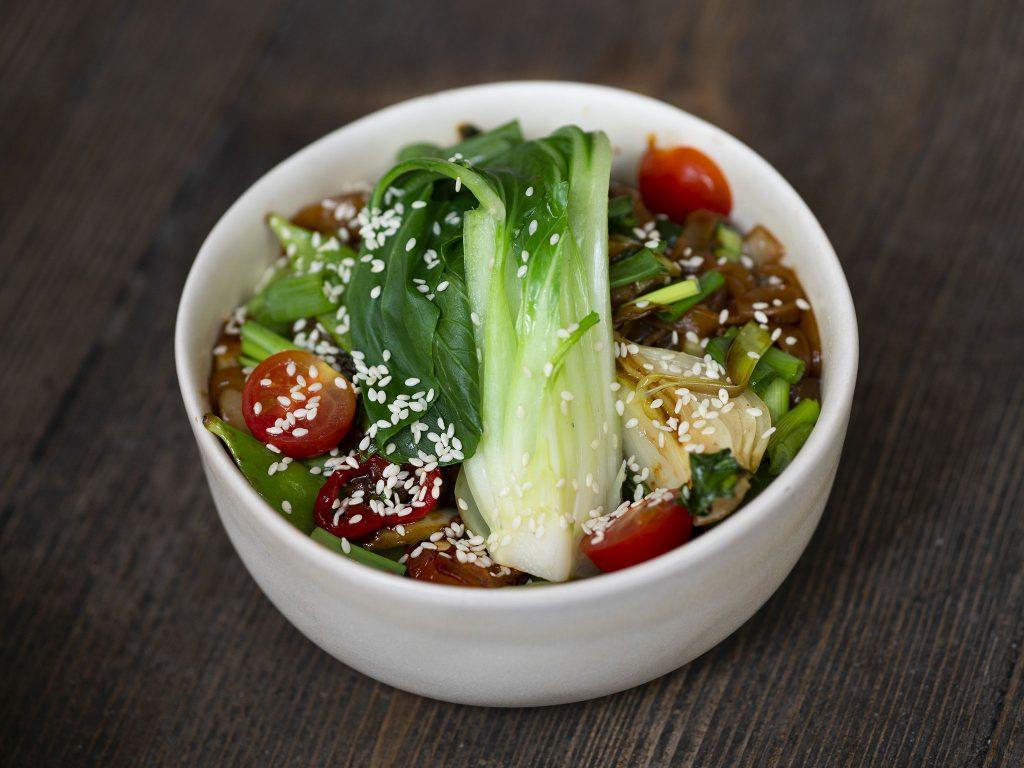 Na zdjęciu widać białą, głęboką, ceramiczną miseczkę, w której znajduje się danie z makaronu ryżowego w kształcie cienkich nitek z kolorowymi warzywami.
