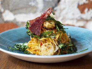 Na zdjęciu widać płaski, błękitny, ceramiczny talerz, na którym ułożona jest porcja makaronu spaghetti z panierowanymi krewetkami, plastrem wysmażonego boczku i rukolą.