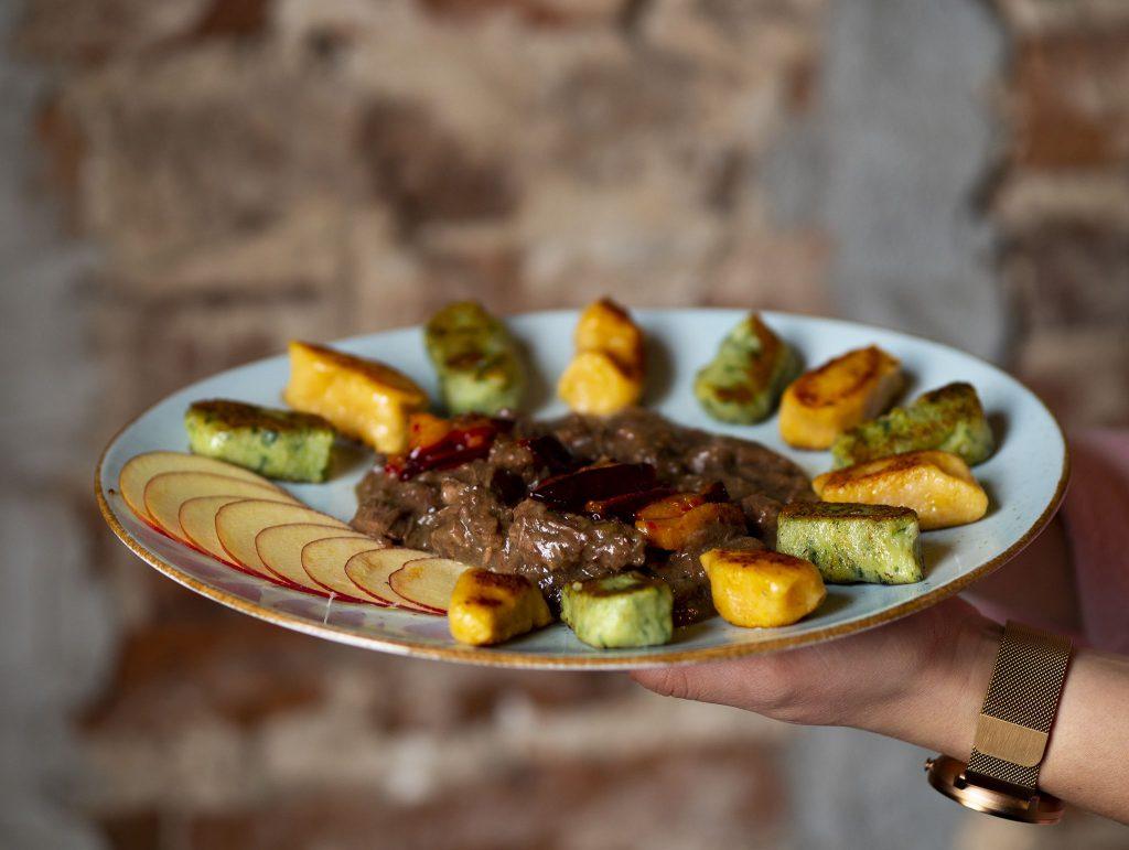 Na zdjęciu widać okrągły talerz, na którym ułożone są kluski w kolorze zielonym i pomarańczowym. Obok klusek znajduje się porcja mięsnego gulaszu i plasterki jabłka.