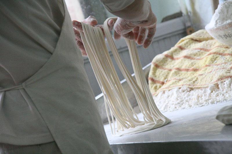 Na zdjęciu widać mężczyznę robiącego ręcznie makaron o długich, cienkich nitkach