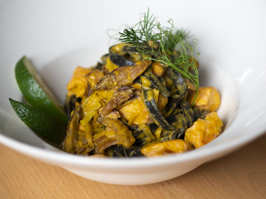 Na zdjęciu widać biały, okrągły, głęboki talerz, w którym znajduje się danie z makaronu w złocisto-żółtym sosie udekorowane ziołami i kiełkami.