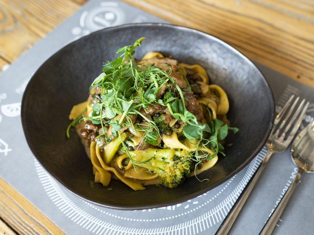 Na zdjęciu widać czarny, głęboki talerz, w którym ułożone jest danie z pszennego makaronu w kształcie szerokich wstążek z mięsem, grzybami leśnymi i brokułami.