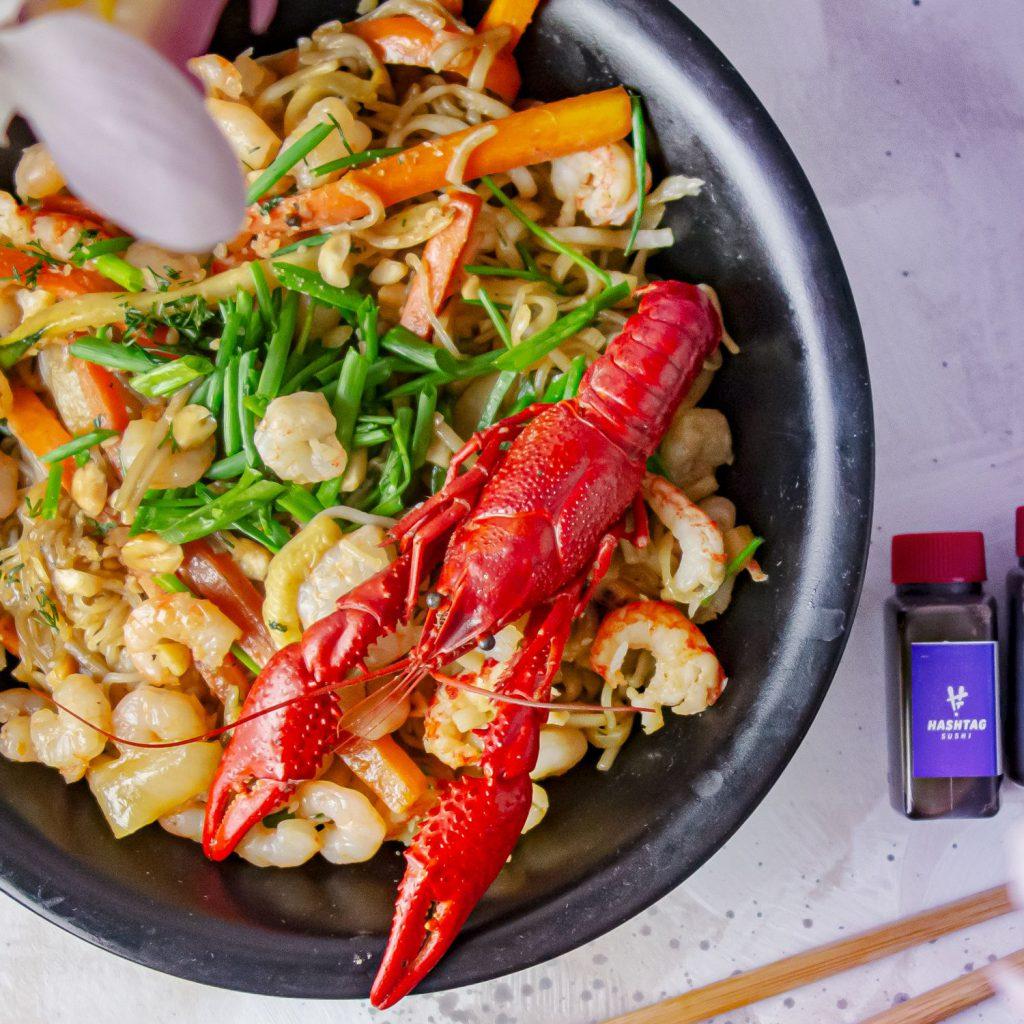 Na zdjęciu widać czarny, kwadratowy talerz, na którym leży danie z makaronu azjatyckiego z warzywami. Na makaronie leży cały rak.
