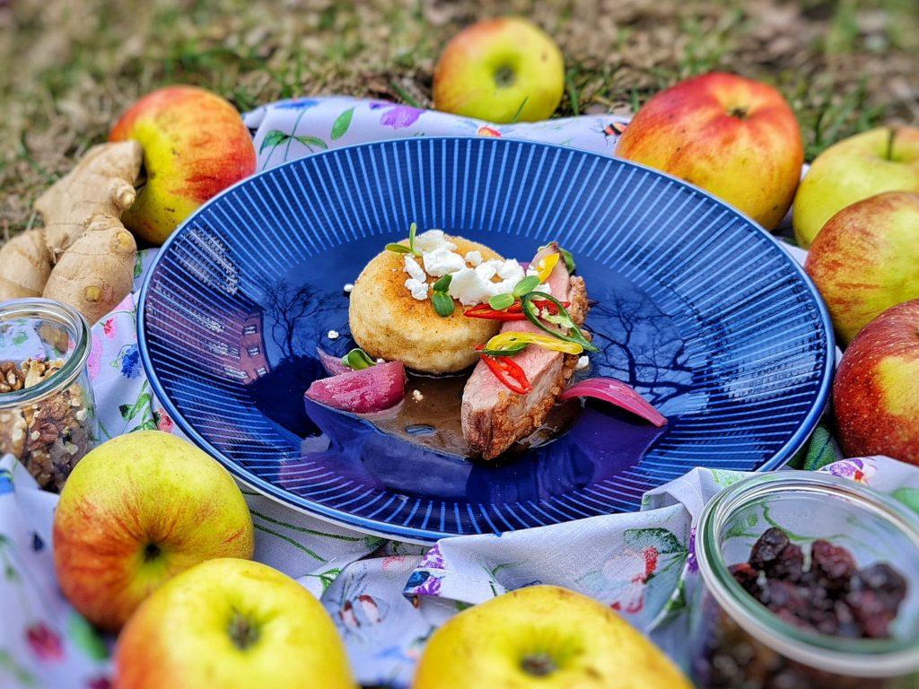 Na zdjęciu widać niebieski, płaski talerz, w którym ułożona jest duża, okrągła, panierowana, smażona kluska i kawałek mięsa.