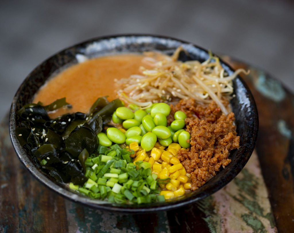 Na zdjęciu widać czarną, ceramiczną miskę, w której znajduje się przypominające zupę danie z makaronem, glonami wakame, siekanym szczypiorem, edamame, kiełkami, kukurydzą i mielonym mięsem.