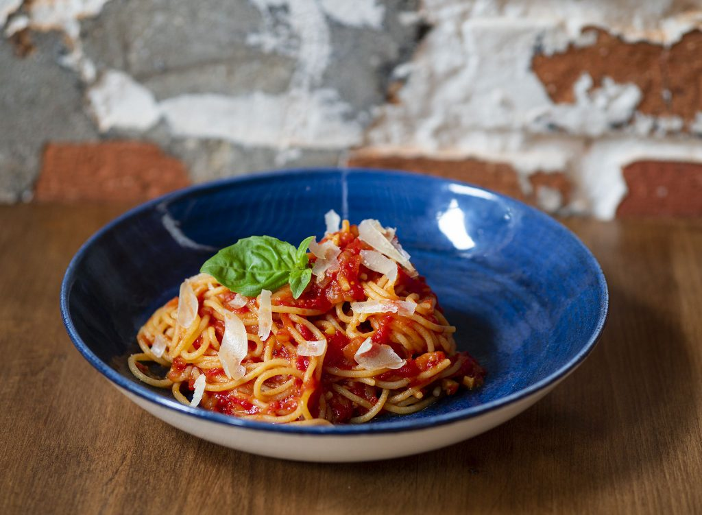 Na zdjęciu widać głęboki talerz, w którym znajduje się makaron spaghetti z sosem z pomidorów udekorowany płatkami parmezanu i listkami bazylii