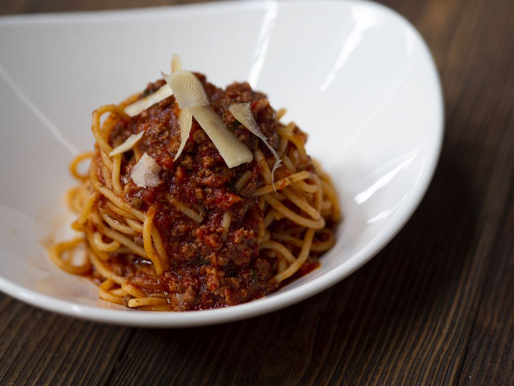Na zdjęciu widać białą, ceramiczną miskę o trójkątnym kształcie. W misce znajduje się makaron spaghetti z mięsno pomidorowym sosem