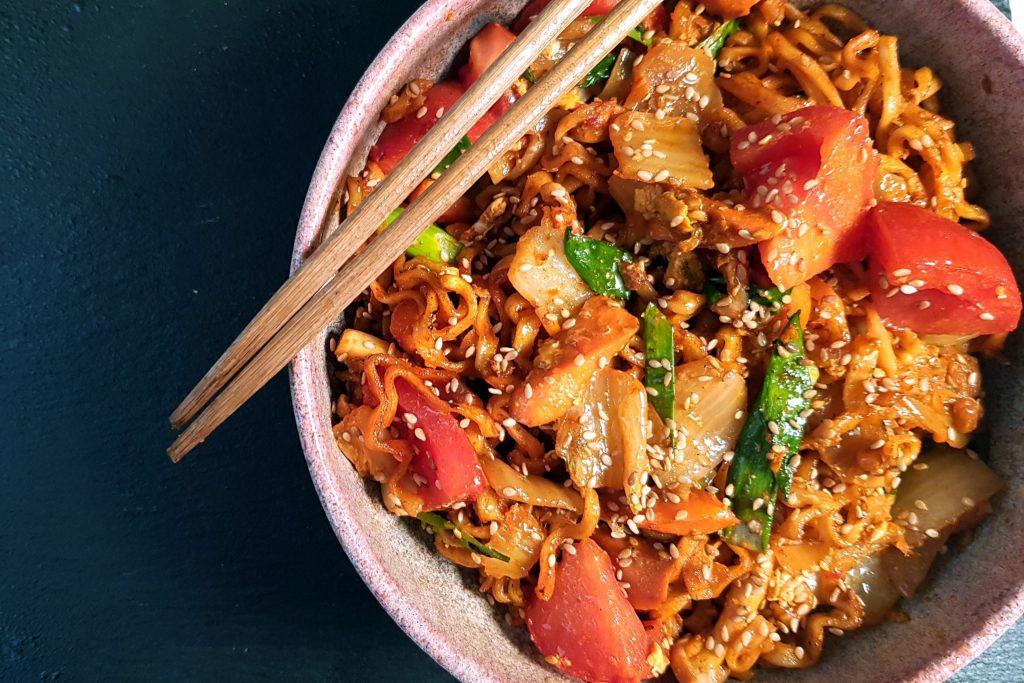 Na zdjęciu widać fragment miski, w której znajduje się danie z makaronu i warzyw obsypane prażonym sezamem