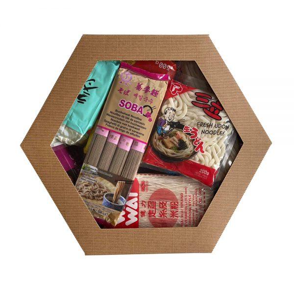Na zdjęciu widać tekturowe pudełko z przeźroczystym wieczkiem. W pudełku znajdują się azjatyckie makarony.