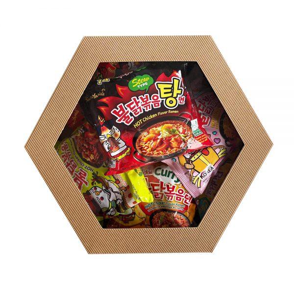 Na zdjęciu widać tekturowe pudełko z przeźroczystym wieczkiem. W pudełku znajdują się koreańskie zupki błyskawiczne w kolorowych opakowaniach.
