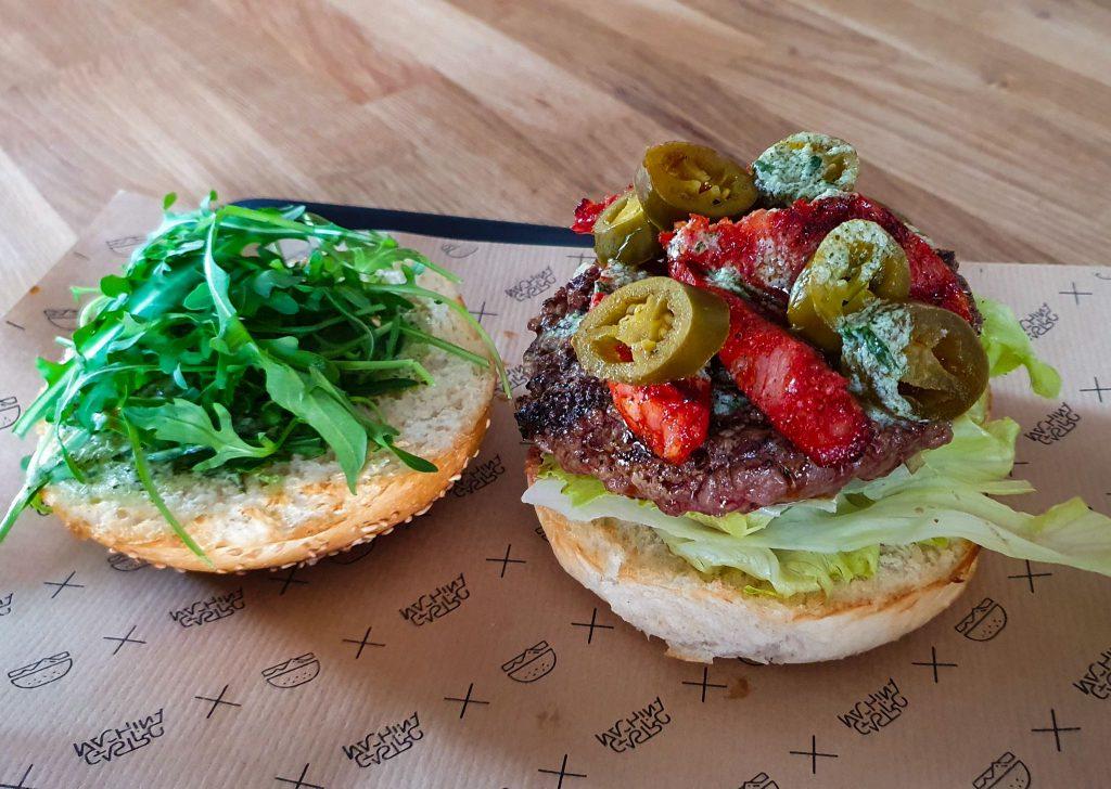 Na zdjęciu widać ułożonego na półmisku burgera z mięsem, kiełbasą chorizo, papryką jalapeno, sałatą i rukolą