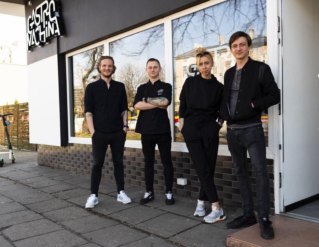 Na zdjęciu widać czwórkę ludzi stojących przed lokalem z szyldem Gastromachina