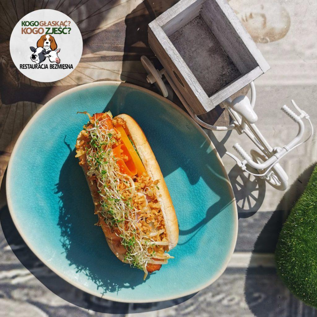 Na zdjęciu widać niebieski talerz na którym leży wegański hot-dog.
