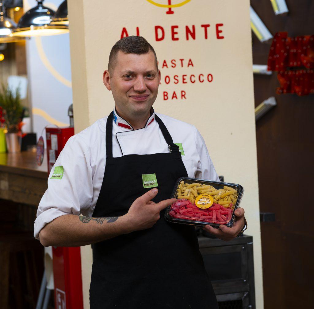 Na zdjęciu widać mężczyznę w kucharskim fartuchu stojącego na tle ściany z logo restauracji Al Dente Pasta & Prosecco Bar. Mężczyzna trzyma w rękach plastikowe pudełko z przezroczystym wieczkiem. W pudełku znajduje się makaron w barwach łódzkich flagi - żółto-czerwony.
