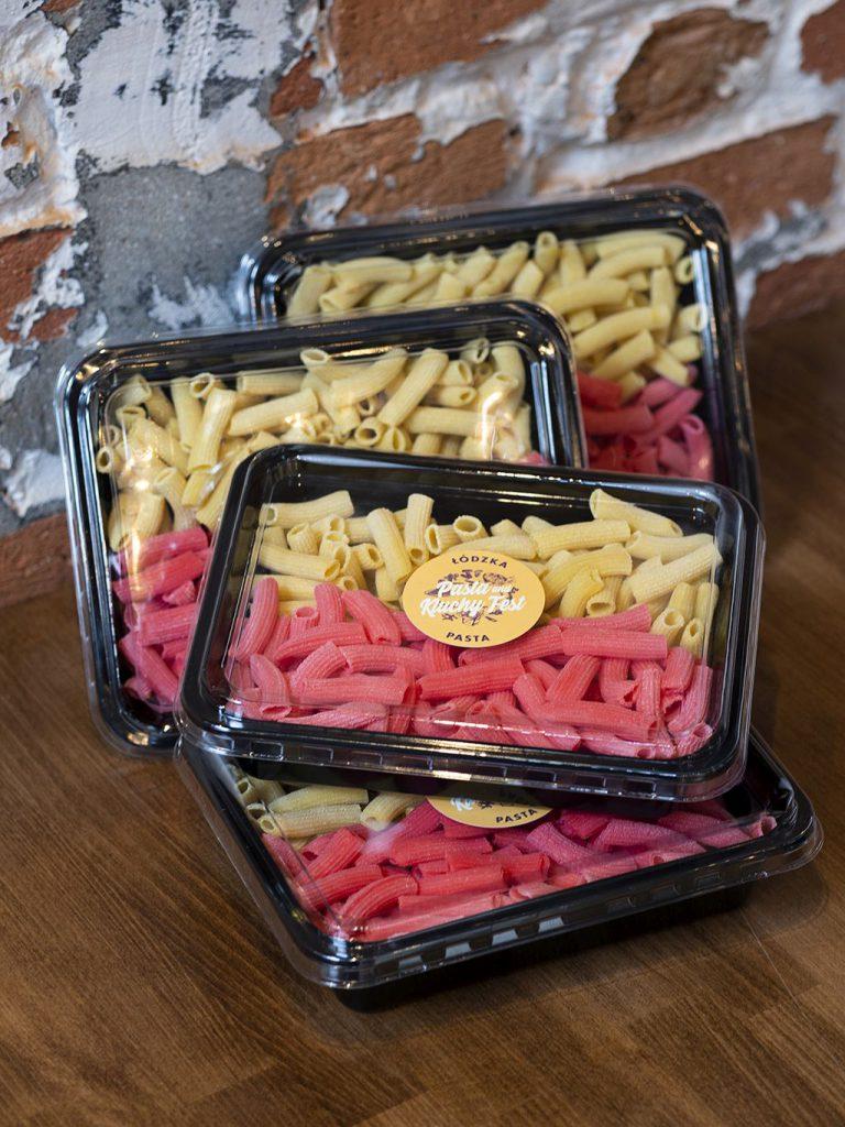 Na zdjęciu widać kilka czarnych, plastikowych pudełek z przezroczystym wieczkiem. W pudełkach znajduje się makaron rigatoni w dwóch kolorach - żółtym i czerwonym. Makarony ułożone są tak, że żółtym jest na górze, a czerwony na dole, co tworzy wrażenie flagi miasta Łódź wykonanej z makaronu. Na wieczku pudełka znajduje się okrągła, żółta naklejka z logo festiwalu Jemy w Łodzi Pasta&Kluchy Fest oraz napisem ŁÓDZKA PASTA