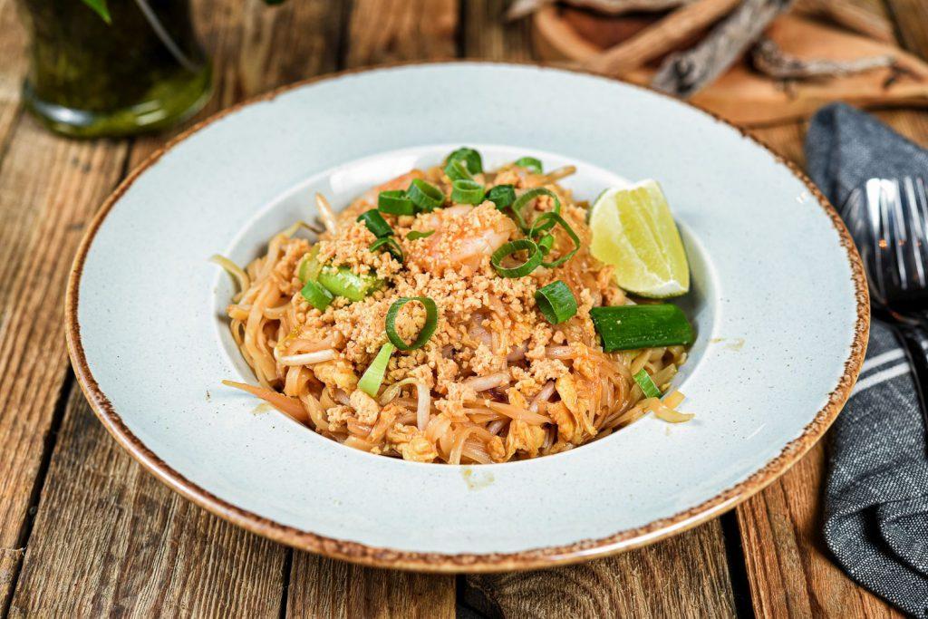 Na zdjęciu widać biały, głęboki talerz, w którym znajduje się danie z makaronu ryżowego z krewetkami, obsypane orzeszkami ziemnymi i pociętą dymką