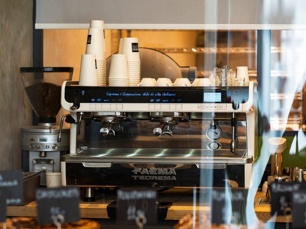 Na zdjęciu widać ekspres do kawy dwukolbowy i ustawione na nim kubki jednorazowe i filiżanki.