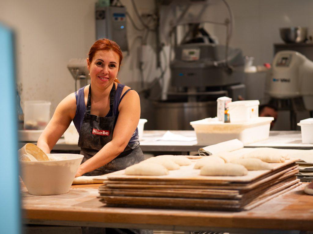Na zdjęciu widać kobietęw fartuchu, która przygotowuje chleb.