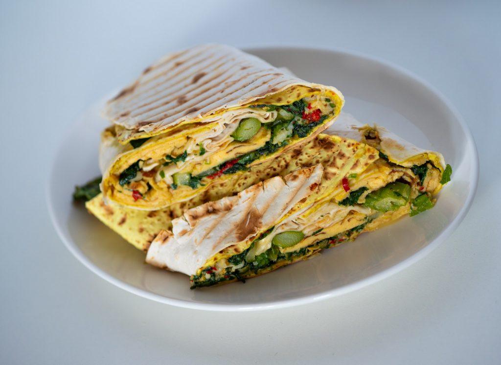 Na zdjęciu widać biały talerz z śniadaniową tortillą.