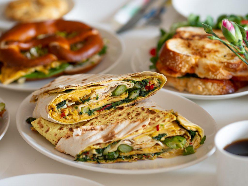 Na zdjęciu widać śniadanie ustawione na stole. Białe talerze i dania: chałkę, precel i tortillę.