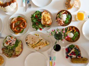 Zdjęcie przedstawia zastawiony stół naczyniami. To obfite śniadanie, które składa się z chałki z dodatkami, precla, tortilli i kolorowych bowli. Do tego kawa i sok.