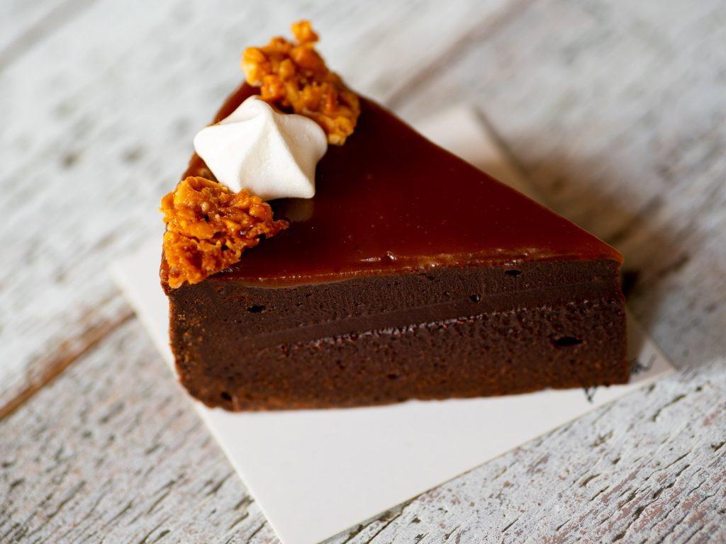 Na zdjęciu widać brownie - porcję mocno czekoladowego ciasta położoną na stole.