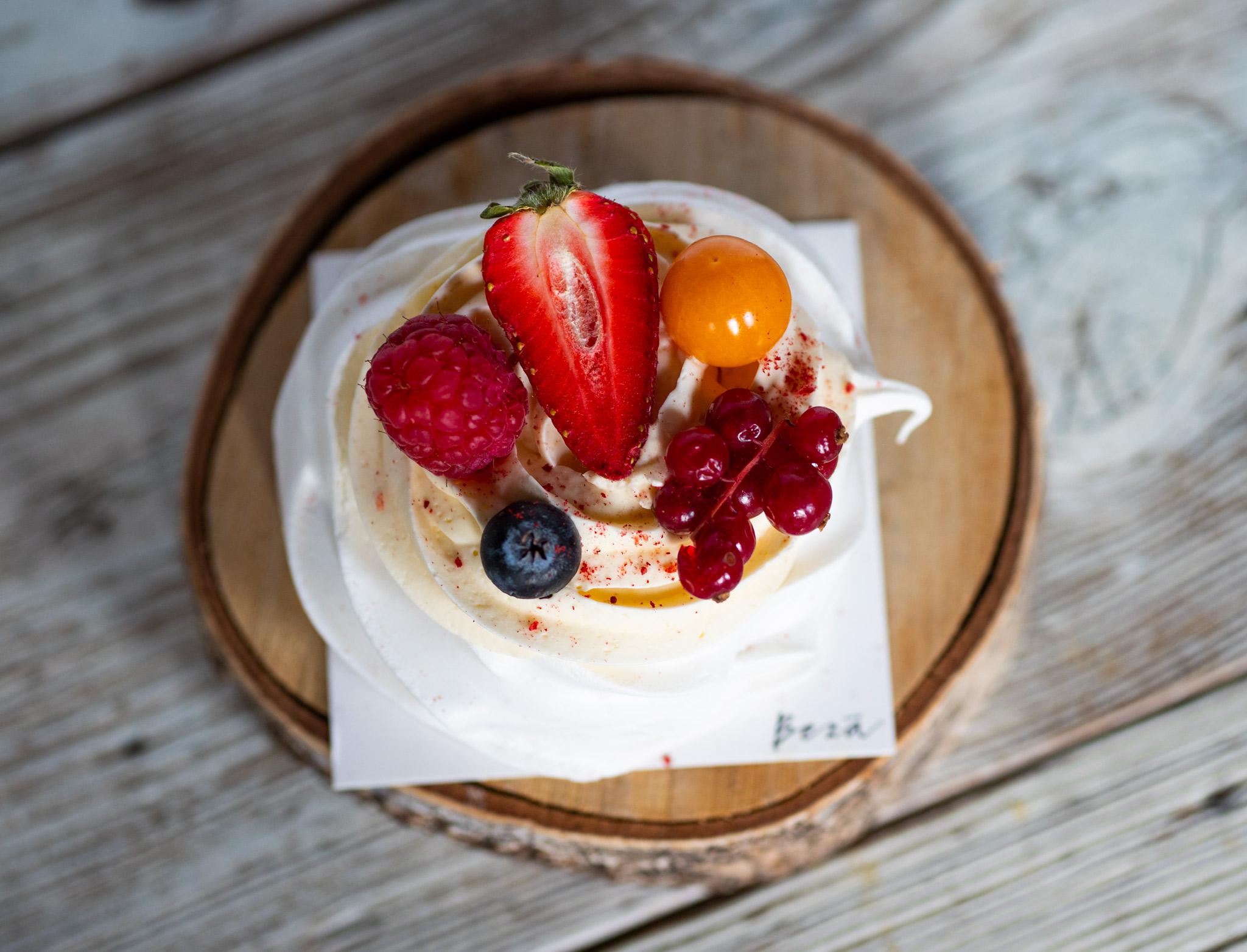 Na zdjęciu widać mini bezę z kremem i owocami ułożoną na drewnianej podstawce, która stoi na stole.