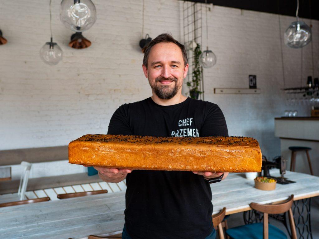 Na zdjęciu widać szefa kuchni restauracji Szwalnia, Przemysława Bednarza. Stoi na tle lokalu, w obydwu rękach trzyma przed sobą wielki bochenek chleba.