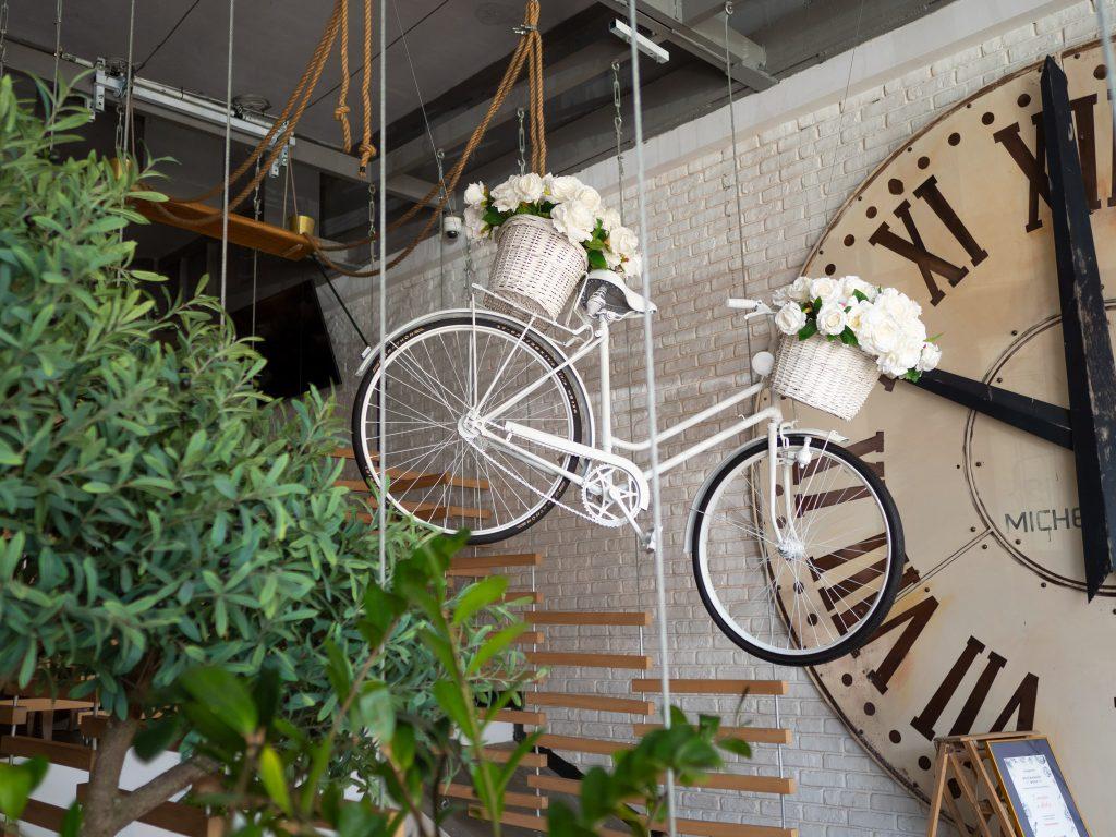 Na zdjęciu widać wejście do lokalu Farina Bianco - na ścianie wisi wielki zegar, pod sufitem podwieszony jest rower pomalowany na biało.
