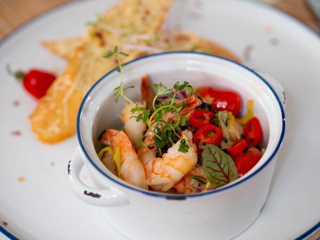 Na zdjęciu widać emaliowane naczynie z krewetkami z chilli w maślanym sosie.