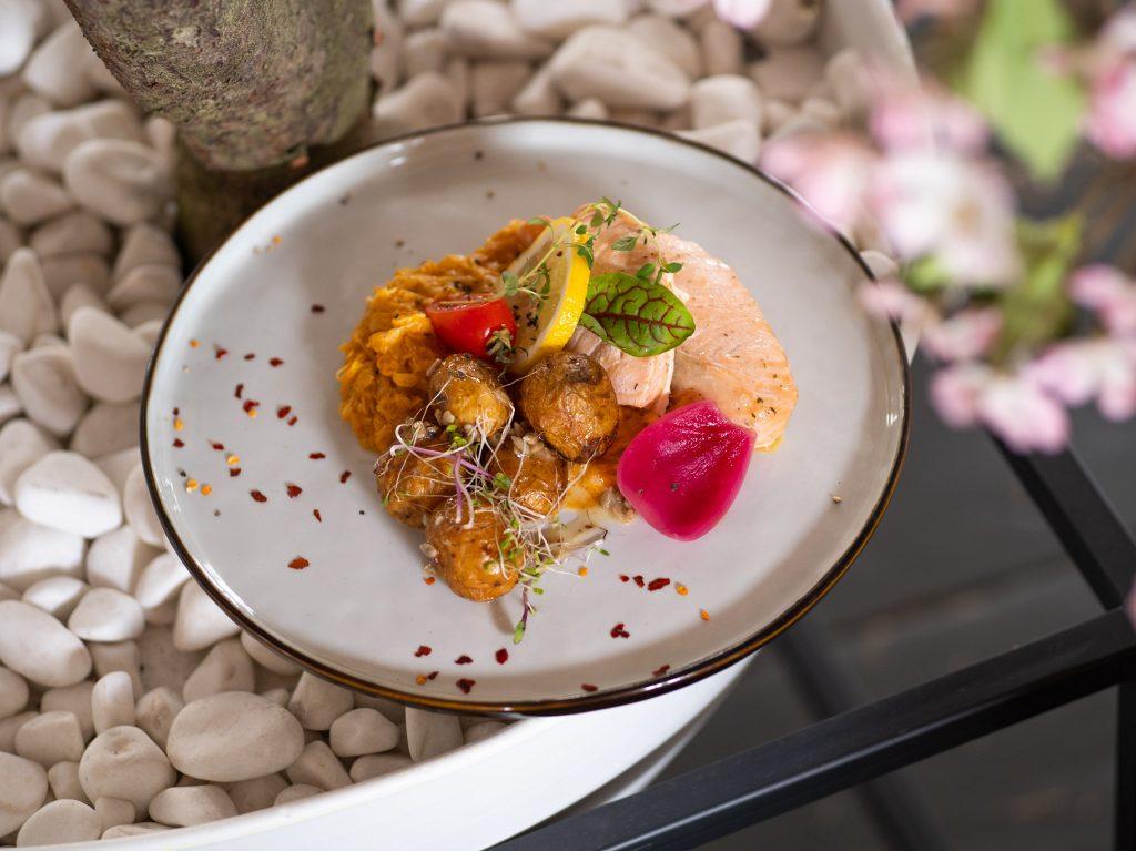 Na zdjęciu widać talerz z daniem - łososiem na kapuście.