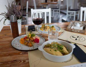 Na zdjęciu widać stół eleganckiej restauracji zastawiony talerzami z daniami i napojami.