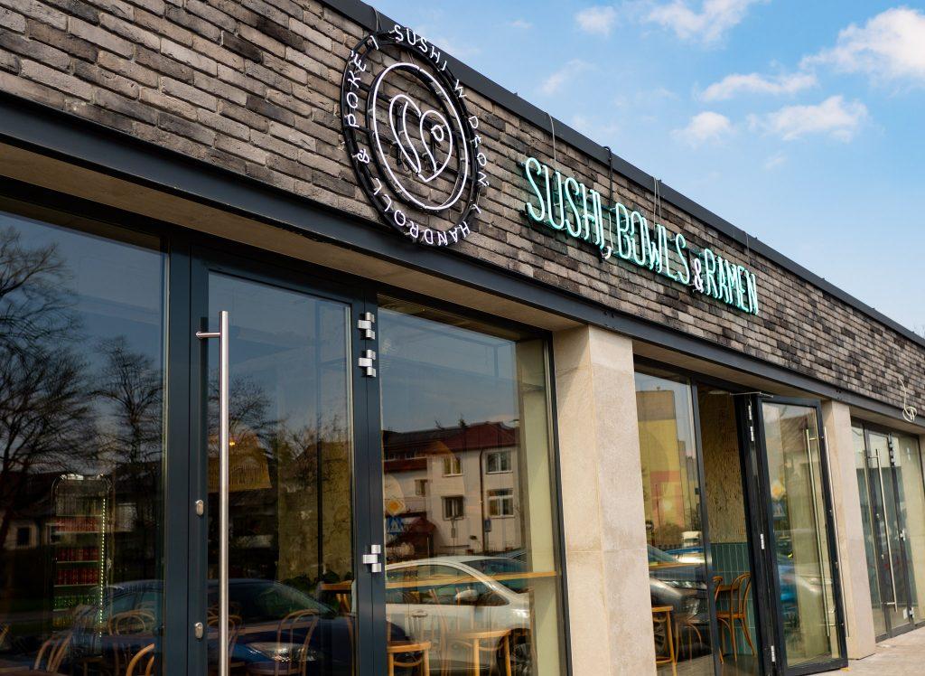 Na zdjęciu widać wejście do lokalu Sushi w dłoń - przeszkloną witrynę i kolorowy neon.