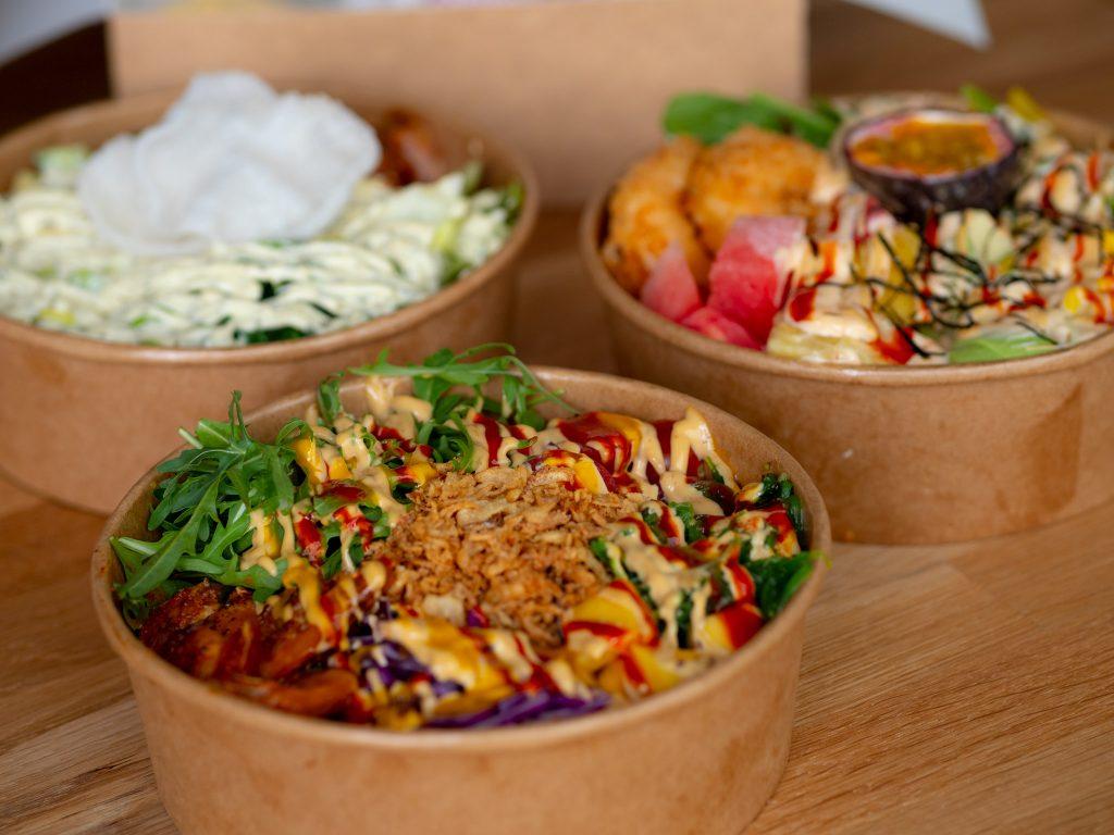 Na zdjęciu widać trzy opakowania na wynos z jedzeniem - poke bowlami.