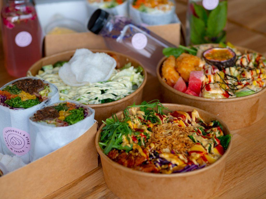 Na zdjęciu widać bowle z jedzeniem i sushiburrito zapakowane na wynos.