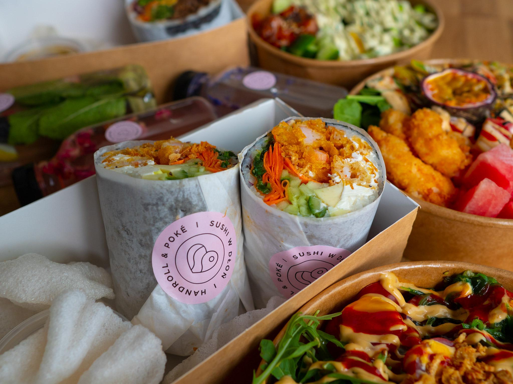 Na zdjęciu widać sushiburrito i bowle w opakowaniach na wynos.