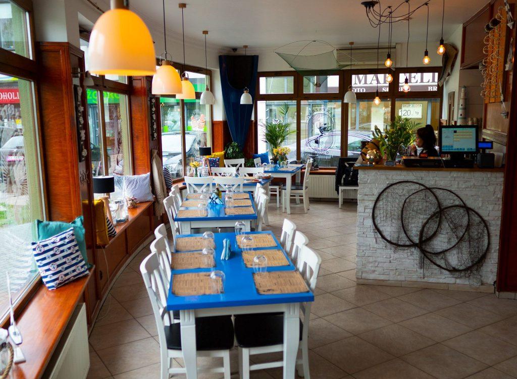 Na zdjęciu widać wnętrze restauracji urządzonej w marynistycznym stylu. Przy błękitnych stołach stoją białe krzesła, ściany i bar zdobią rybackie sieci.