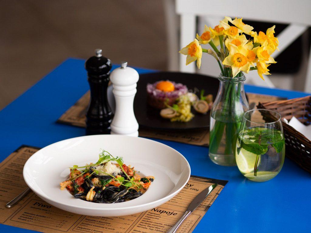 Na zdjęciu widać stół w restauracji nakryty talerzami z jedzeniem. Obok talerzy stoi wazon ze świeżymi kwiatami, solniczka i pieprzniczka