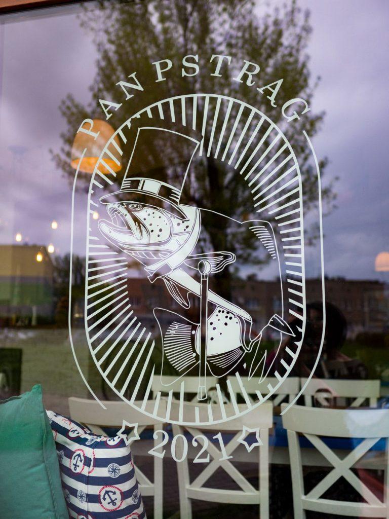 Na zdjęciu widać fragment przeszklonej witryny z białą naklejką z logo restauracji Taki Pan Pstrąg