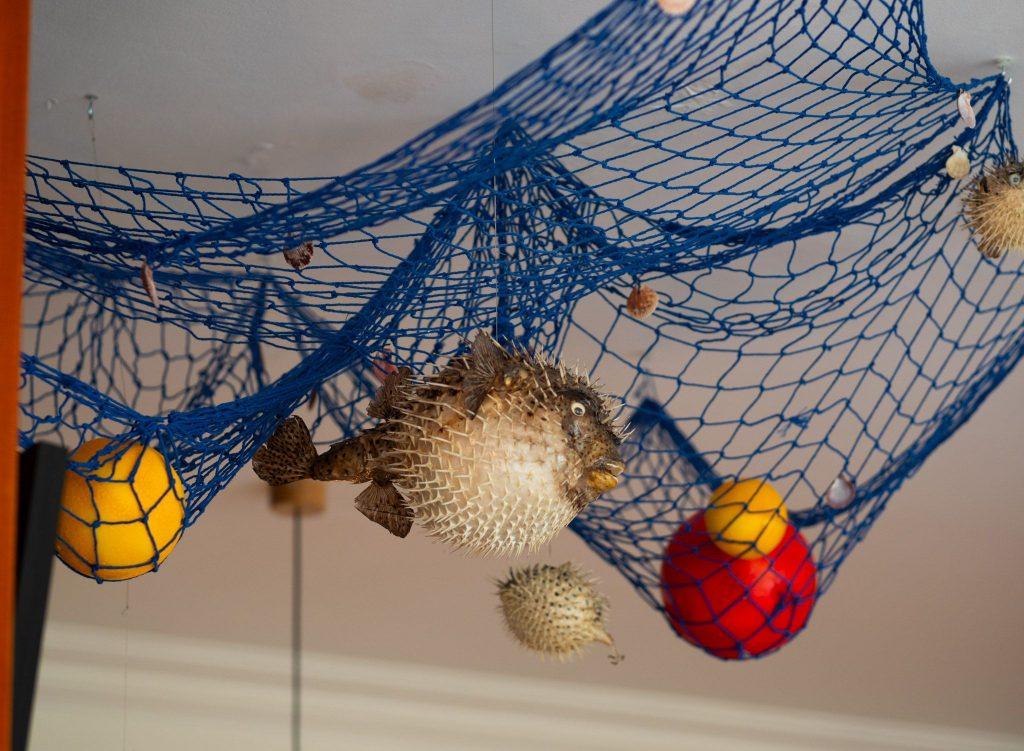 Na zdjęciu widać podwieszoną pod sufitem, niebieską sieć rybacką, a w niej sztuczne ryby, muszle i inne morskie akcesoria dekoracyjne.